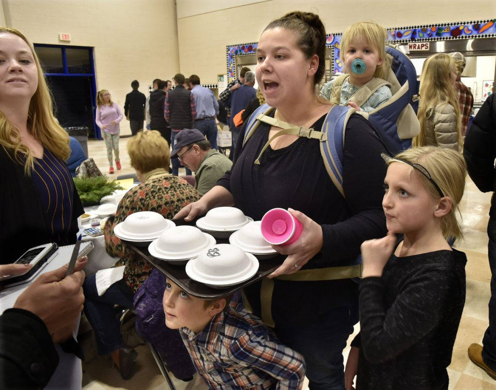 Rachael McKenney carries her youngest daughter, Olivia, while serving slices of pie, as her son, Liam, peers from under the tray at the Messalonskee Thanksgiving Day Community Meal on Thursday. McKenney's daughter Kaydence is at right and her sister Jenna Nesbit is at left.
