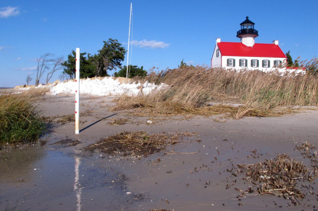 "The waters of Delaware Bay encroach on East Point Lighthouse in Maurice River Township, N.J. Because of rising seas, ""this lighthouse is in incredible danger,"" says advocate Nancy Patterson. ""We need to do something – now – while there's still something to save."""