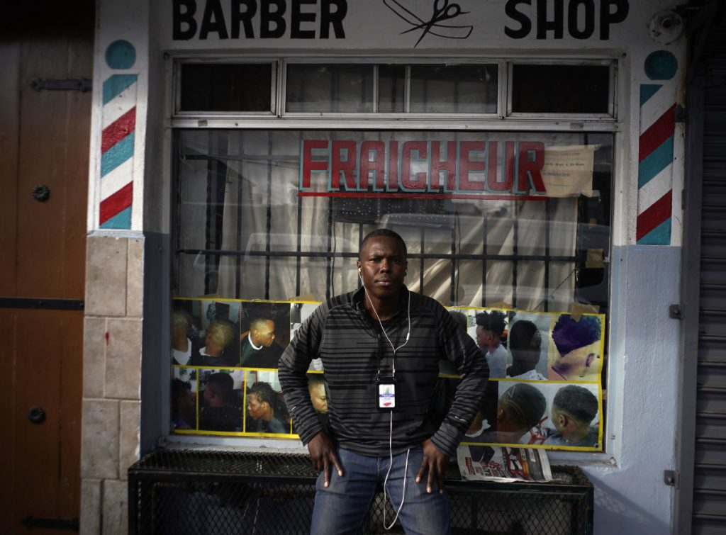 Philocles Julda, 44, stands in front of a Haitian barbershop in Tijuana, Mexico. Julda belongs to a group of Haitian immigrants who offer their peers resources such as language lessions and money management tips.