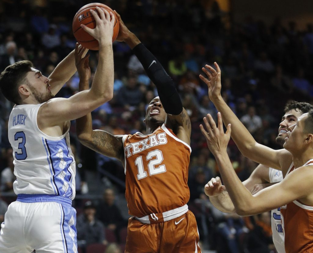 Andrew Platek of North Carolina, left, and Kerwin Roach II of Texas compete for a rebound Thursday during the first half of Texas' 92-89 victory against the seventh-ranked Tar Heels at Las Vegas. The unranked Longhorns improved to 5-0 and dropped the Tar Heels to 5-1.