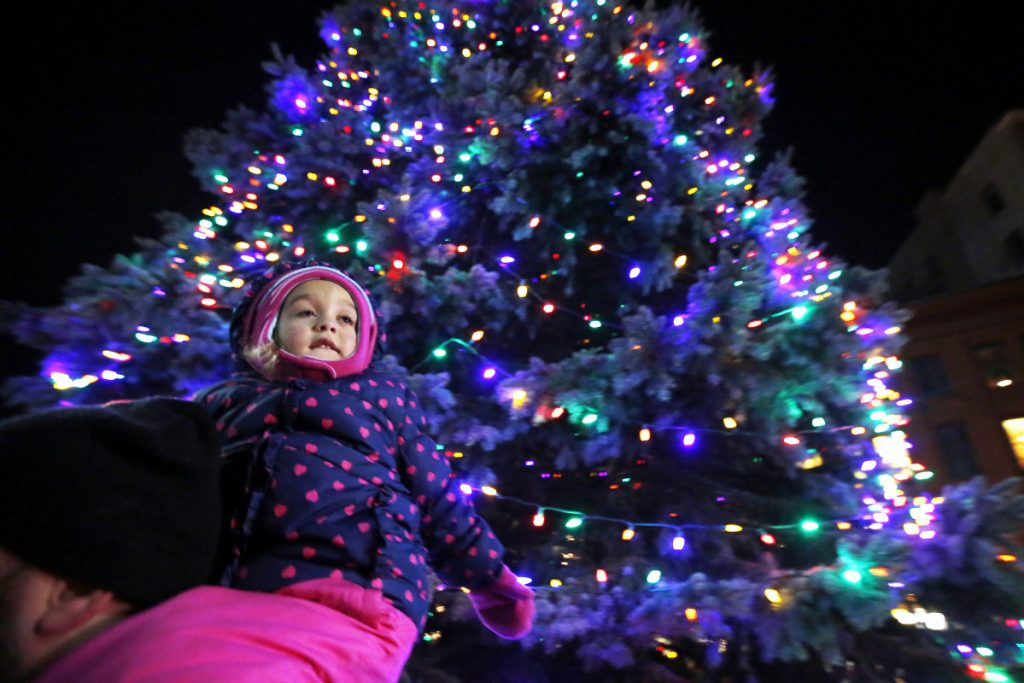 Aleigh Fauth, 3, of South Portland, rides on father Brian Fauth's shoulders just after the tree was lit on Friday in Monument Square in Portland.