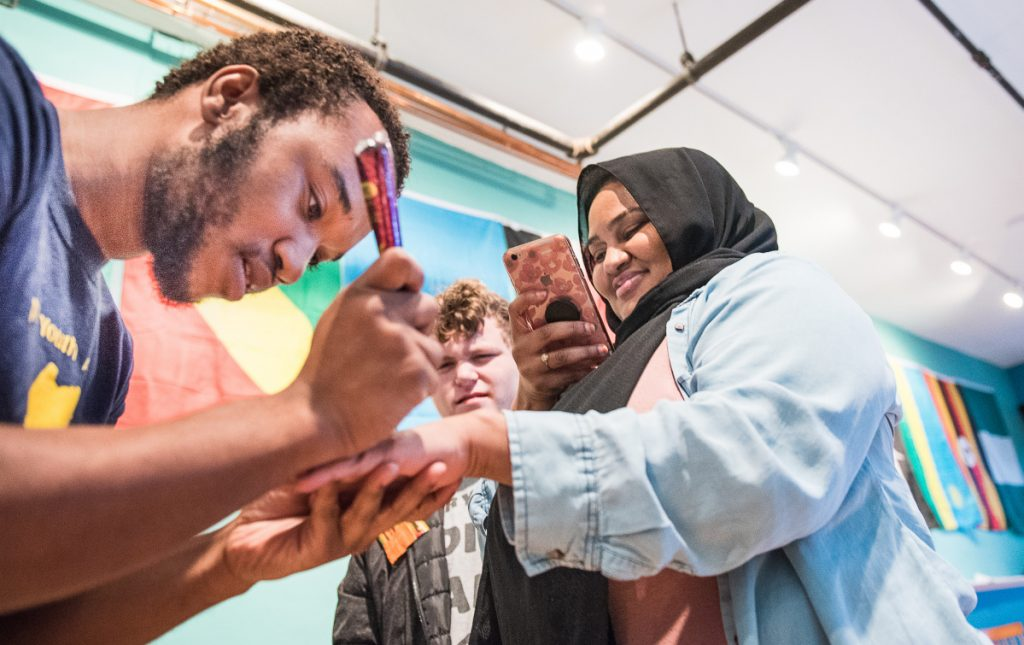 "African Youth Alliance Vice President Djamal Maldoum draws henna on Hani Mohamed of Auburn during Friday's open house at the new organization's ""welcoming place"" on Lisbon Street in Lewiston."