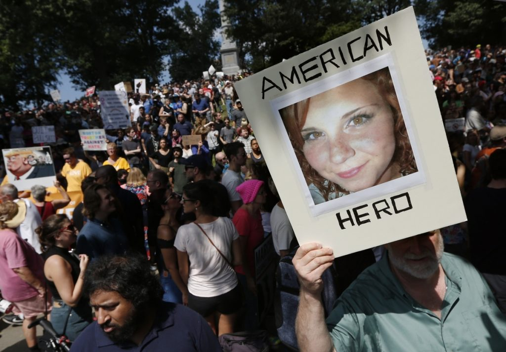 "A counter-protester holds a photo of Heather Heyer on Boston Common at a ""Free Speech"" rally organized by conservative activists, in Boston. Jury selection is set to begin in the trial of James Alex Fields Jr., accused of killing Heyer during a white nationalist rally in Charlottesville in 2017."