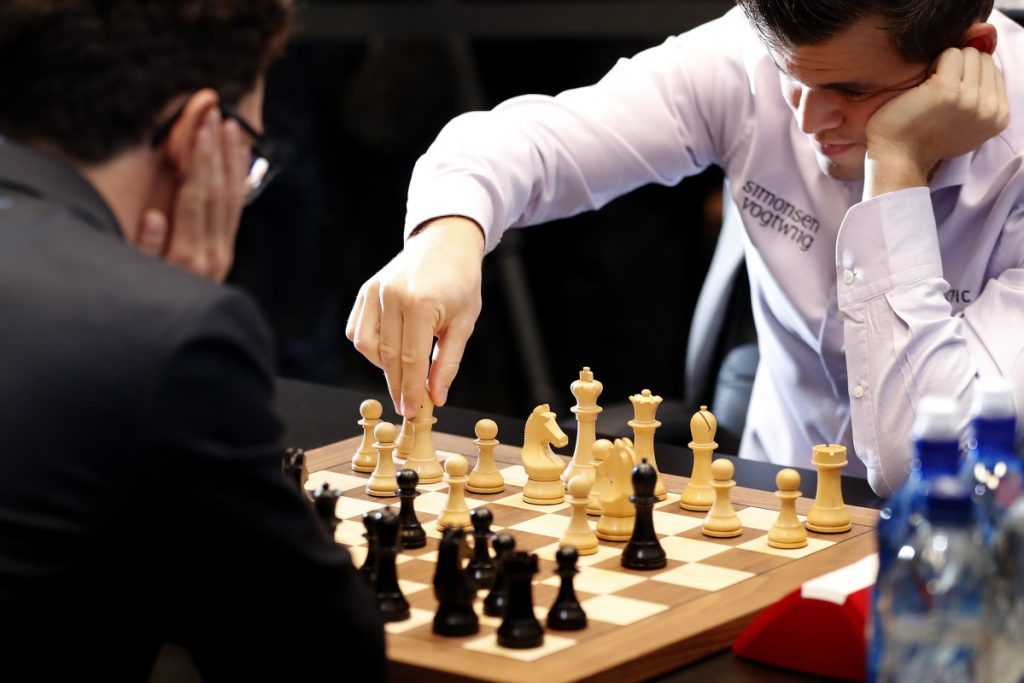 Reigning chess world champion, Norway's Magnus Carlsen, makes a move while playing against American Fabiano Caruana in the final day of the world chess championship in London.