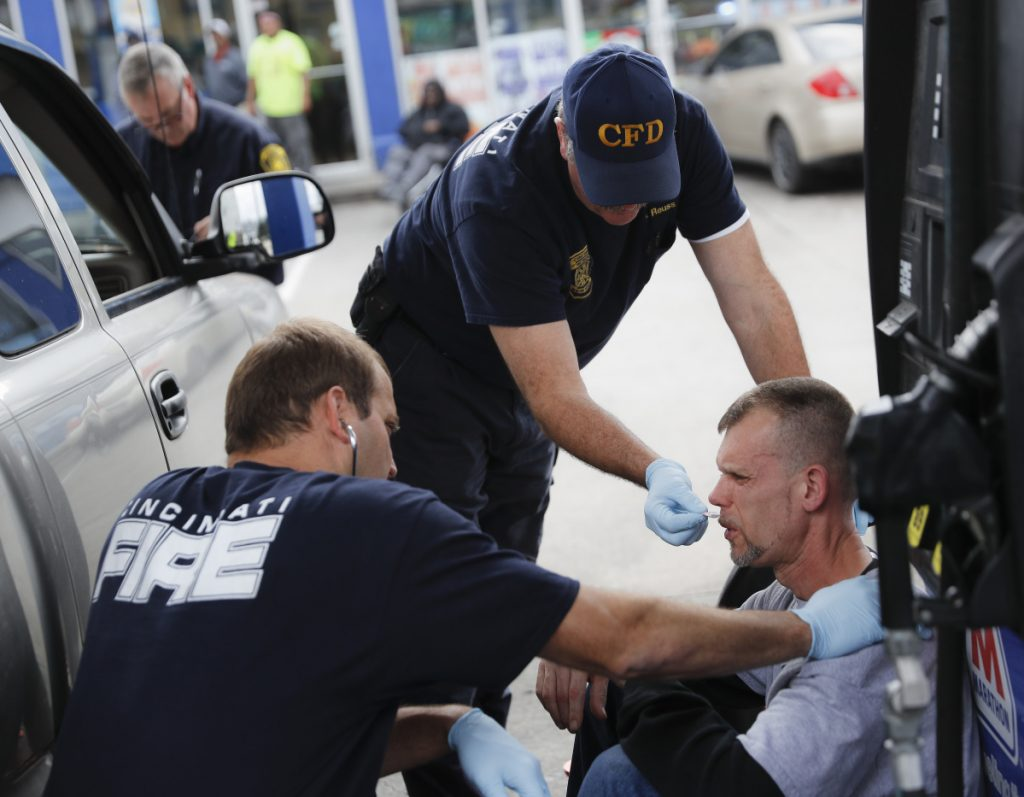 Medics with the Cincinnati Fire Department work to keep a possible overdose victim awake after administering Naloxone while responding to a report at a gas station in 2017 in downtown Cincinnati.