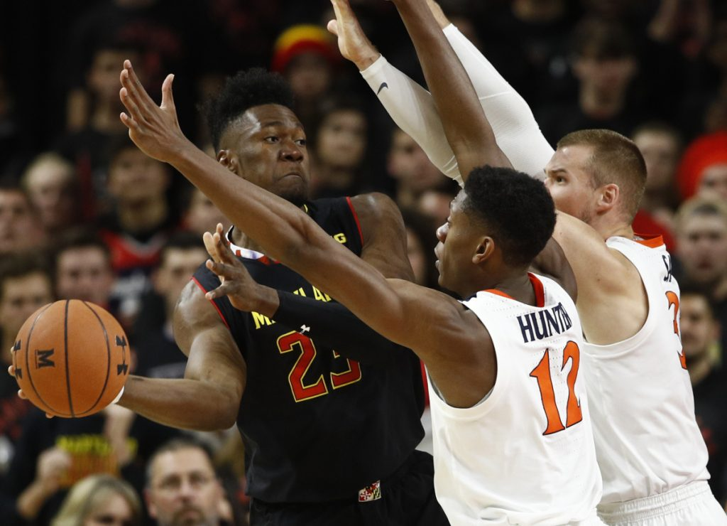 Maryland's Bruno Fernando, left, looks for a teammate as he is pressured by De'Andre Hunter, center, and Jack Salt during Virginia's 76-71 win Wednesday.
