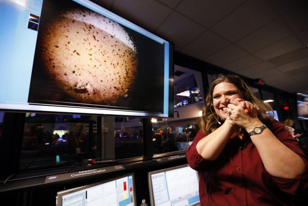 An engineer at NASA's Jet Propulsion Laboratory celebrates next to an image of Mars sent from the InSight lander shortly after it landed on the red planet Monday. Only about 40 percent of Mars landings are successful.