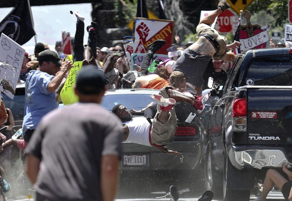 "People fly into the air as a vehicle is driven into a group of protesters demonstrating against a white nationalist rally in Charlottesville, Va., on Aug. 12, 2017. James Alex Fields Jr. is accused of driving into the crowd, killing one person. At left, a protester holds a photo of victim Heather Heyer at a ""Free Speech"" rally in Boston. Associated Press"