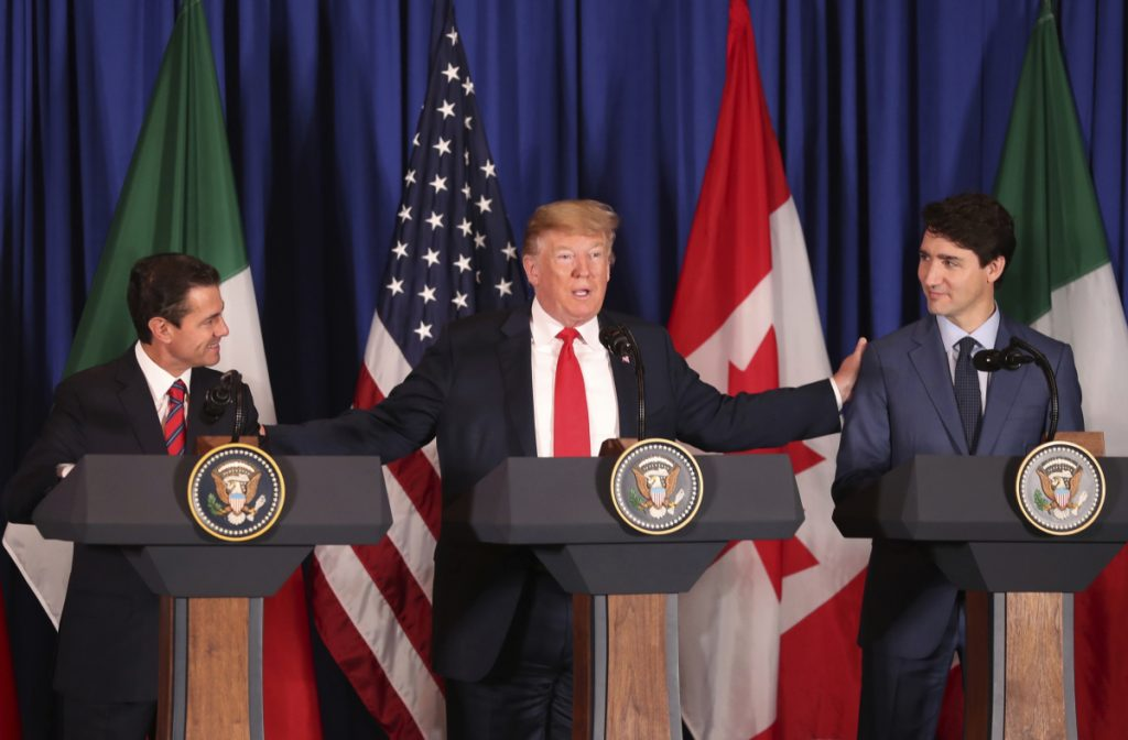 President Trump reaches out to Mexico's President Enrique Pena Nieto, left, and Canada's Prime Minister Justin Trudeau as they prepare to sign a new United States-Mexico-Canada Agreement that is replacing the NAFTA trade deal, during a ceremony at a hotel before the start of the G-20 summit in Buenos Aires, Argentina, on Friday.