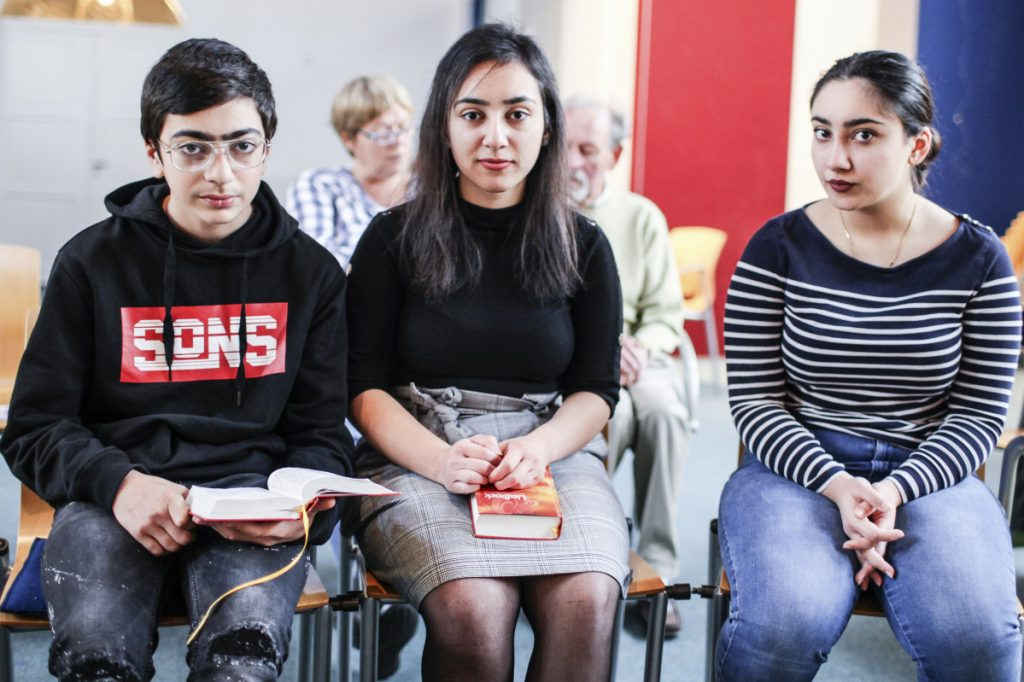 Sisters Hayarpi, 21, right, Warduhi, 19, center, and their 15-year-old brother, Seyran Tamrazyan, pose for a photo inside the Bethel Church in The Hague, Netherlands, where a rotating roster of preachers has led a nonstop service.