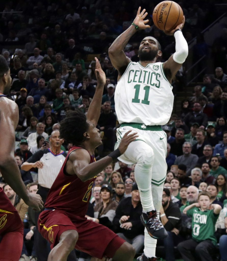 Kyrie Irving, who finished with 29 points in three quarters for the Boston Celtics, shoots over Collin Sexton of Cleveland during Boston's 128-95 win.