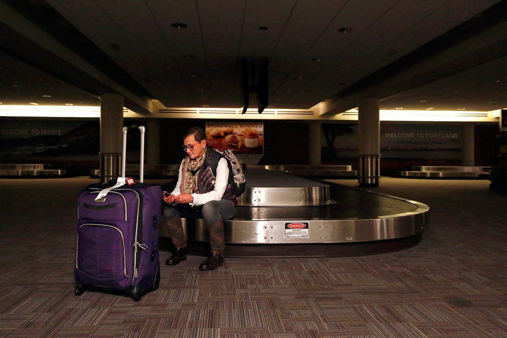 Mary Tippet, who had just arrived at Portland International Jetport from her home state of Colorado, waits for her ride to arrive in the baggage area under emergency lighting. Her friends were stuck in heavy traffic when part of Congress Street was closed after a truck hit a utility pole, causing a power outage at the jetport and nearby areas.