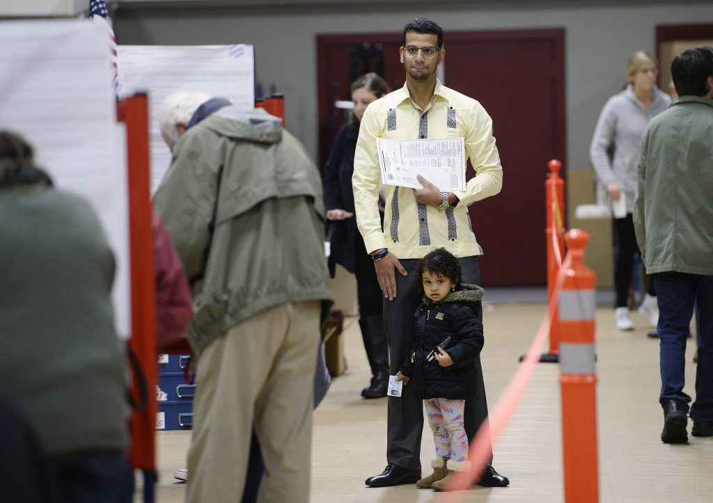 Luis Sanchez waits for a voting booth to open up as he votes with his daughter Sophia, 2, at the Saco Community Center on Tuesday. It was the first vote in a U.S. election for Sanchez, who is originally from the Dominican Republic and became an American citizen on Nov. 2. He took his time filling out his ballot as Sophia played around his feet.