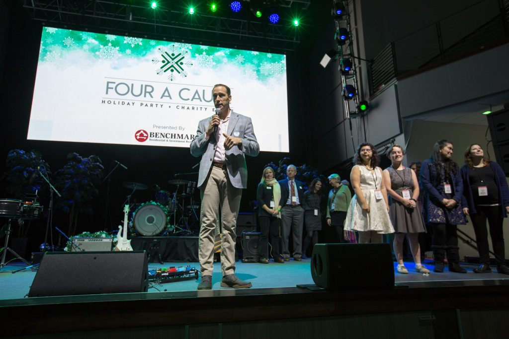 Tom Landry, owner/broker of Benchmark Residential & Investment Real Estate, addresses the crowd at Benchmark's 2017 Four A Cause benefit event at AURA.