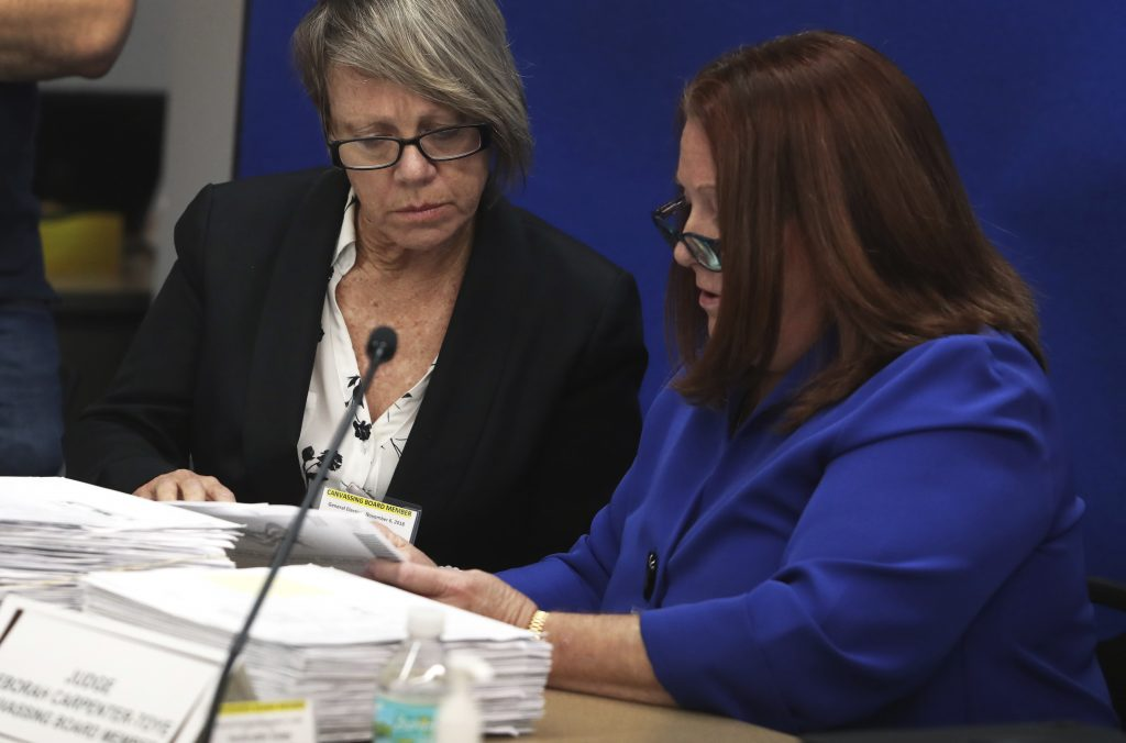 Canvassing Board members, Judge Betsy Benson, left, and Judge Deborah Carpenter-Toye look over signatures on ballots at the Broward County Supervisor of Elections in Lauderhill, Fla., Thursday, November 8, 2018.