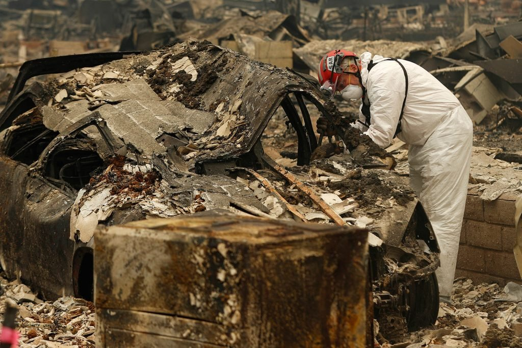 A search-and-rescue worker searches a car for human remains Tuesday at a trailer park in Paradise, Calif., that was burned out by the Camp Fire.
