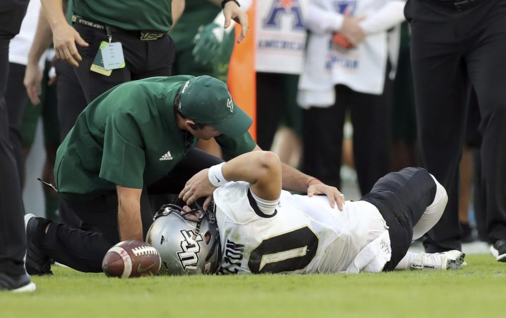 A trainer from South Florida attends to Central Florida quarterback McKenzie Milton after he went down with an apparent knee injury during the first half Friday in Tampa, Florida.