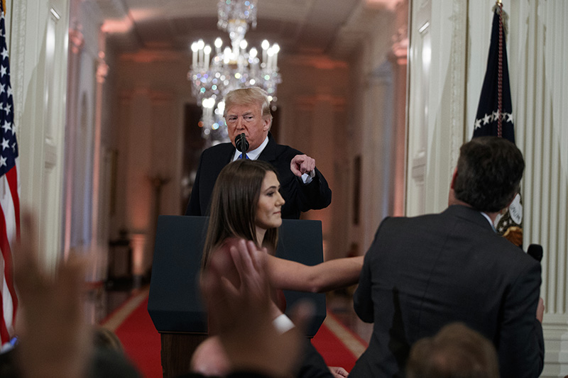 Donald Trump watches as a White House aide reaches to take away a microphone from CNN journalist Jim Acosta during a news conference at the White House in November.
