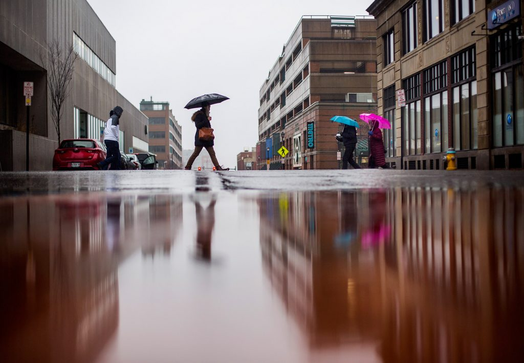 Pedestrians cross the intersection of Congress and Elm streets in Portland on a wet Friday.