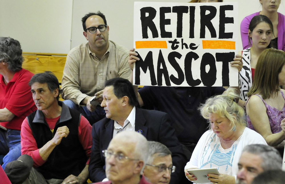 """Mark Roman holds a sign protesting use of the term """"Indian"""" for SAD 54 sports teams during a forum in Skowhegan on May 4, 2015. At far left is former chief Penobscot tribal chief Barry Dana, of Solon."""