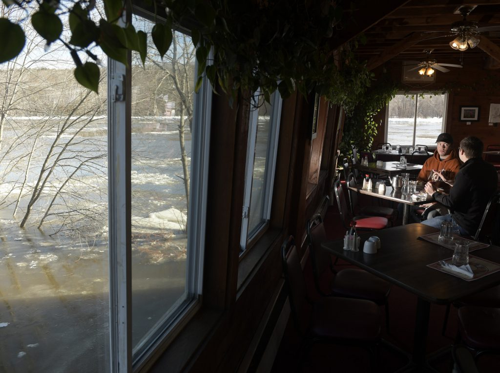 Jake Levesque, left, and Dylan Sirios eat lunch Jan. 14 at the Lucky Garden restaurant as the flooding Kennebec River surrounds them in Hallowell.