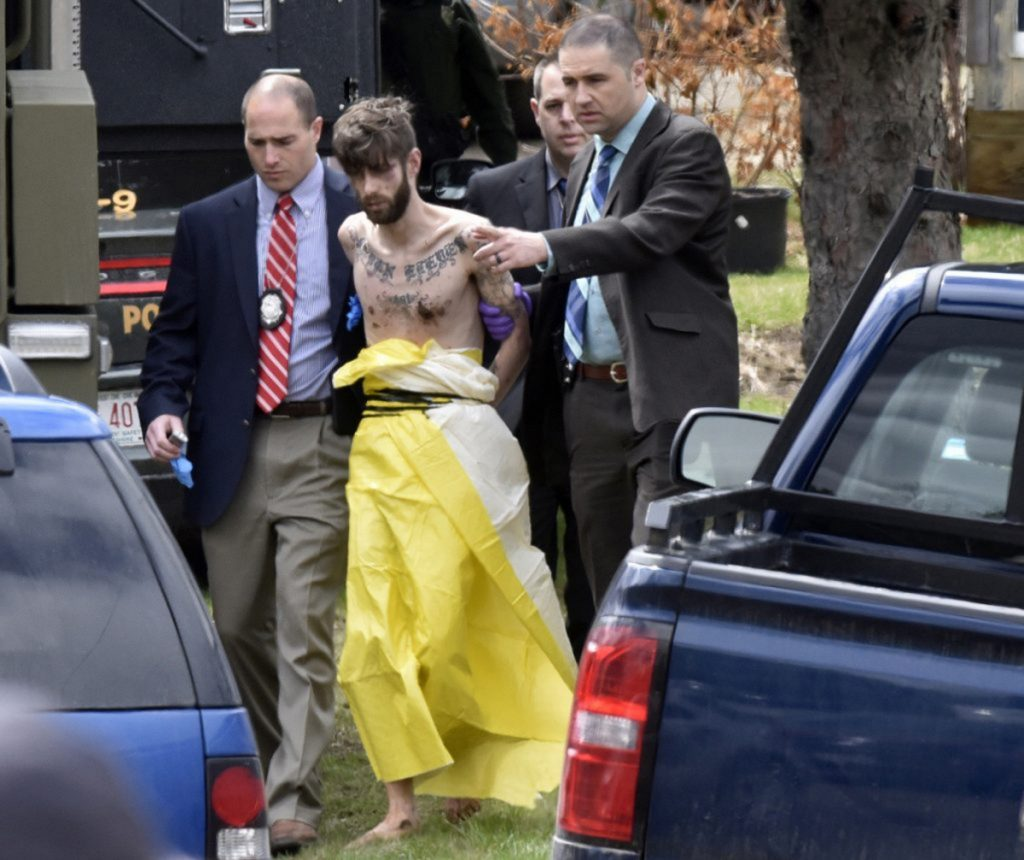 Authorities lead John Williams away in handcuffs April 28.