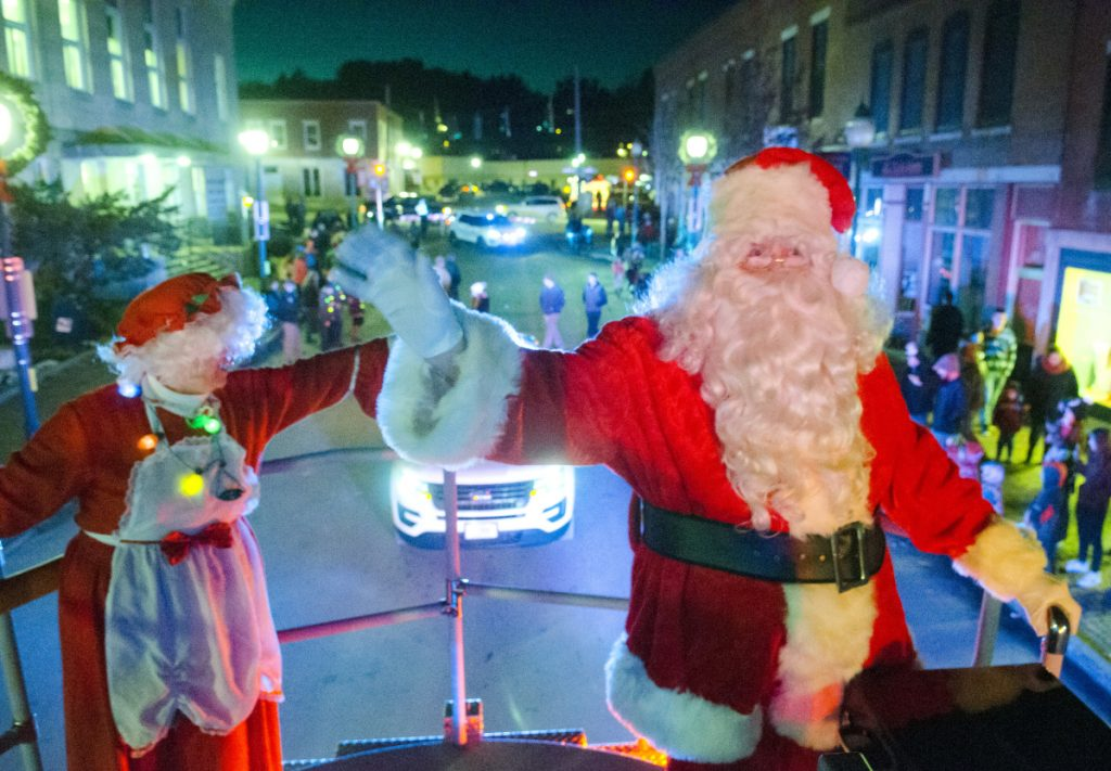 Mrs. Claus and Santa Claus wave at spectators Saturday as they ride down Water Street on the Gardiner Fire Department's Ladder 1 truck in Gardiner. Staff photo by Joe Phelan