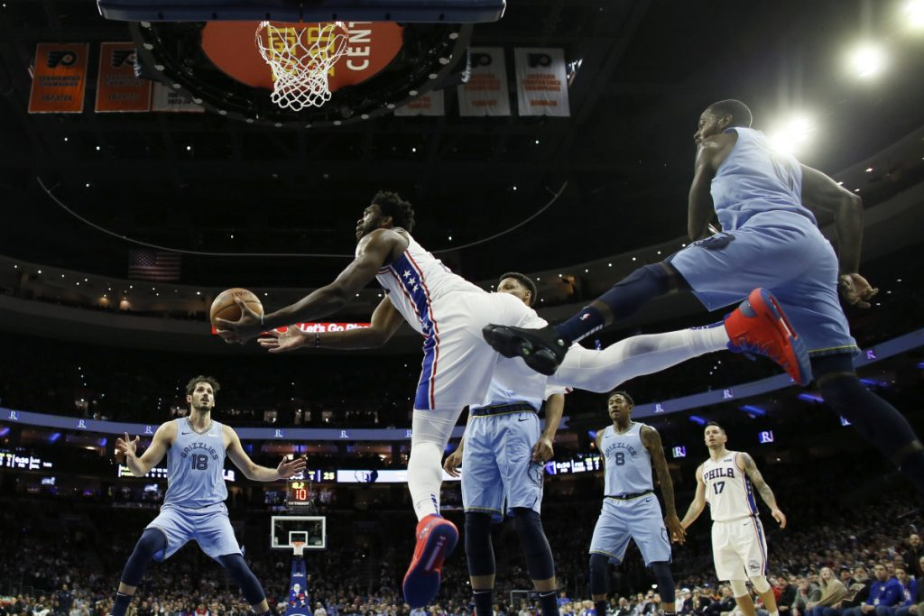 Joel Embiid of the Philadelphia 76ers, center, goes up for a shot after slipping past JaMychal Green of the Memphis Grizzlies during the first half of Philadelphia's 103-95 victory Sunday night.
