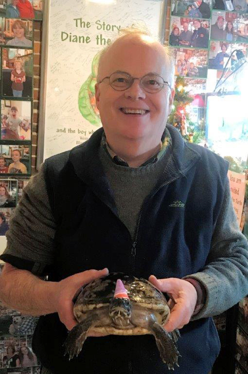 Diane the Turtle, wearing a party hat, celebrates her 50th birthday with her owner, Jim Tonner, at a gift shop he and his brother Brad run in Bristol, N.H. The turtle was given to Jim Tonner when he was 12 and being treated for hip arthritis at his home in Braintree, Mass. (Brad Tonner via AP)