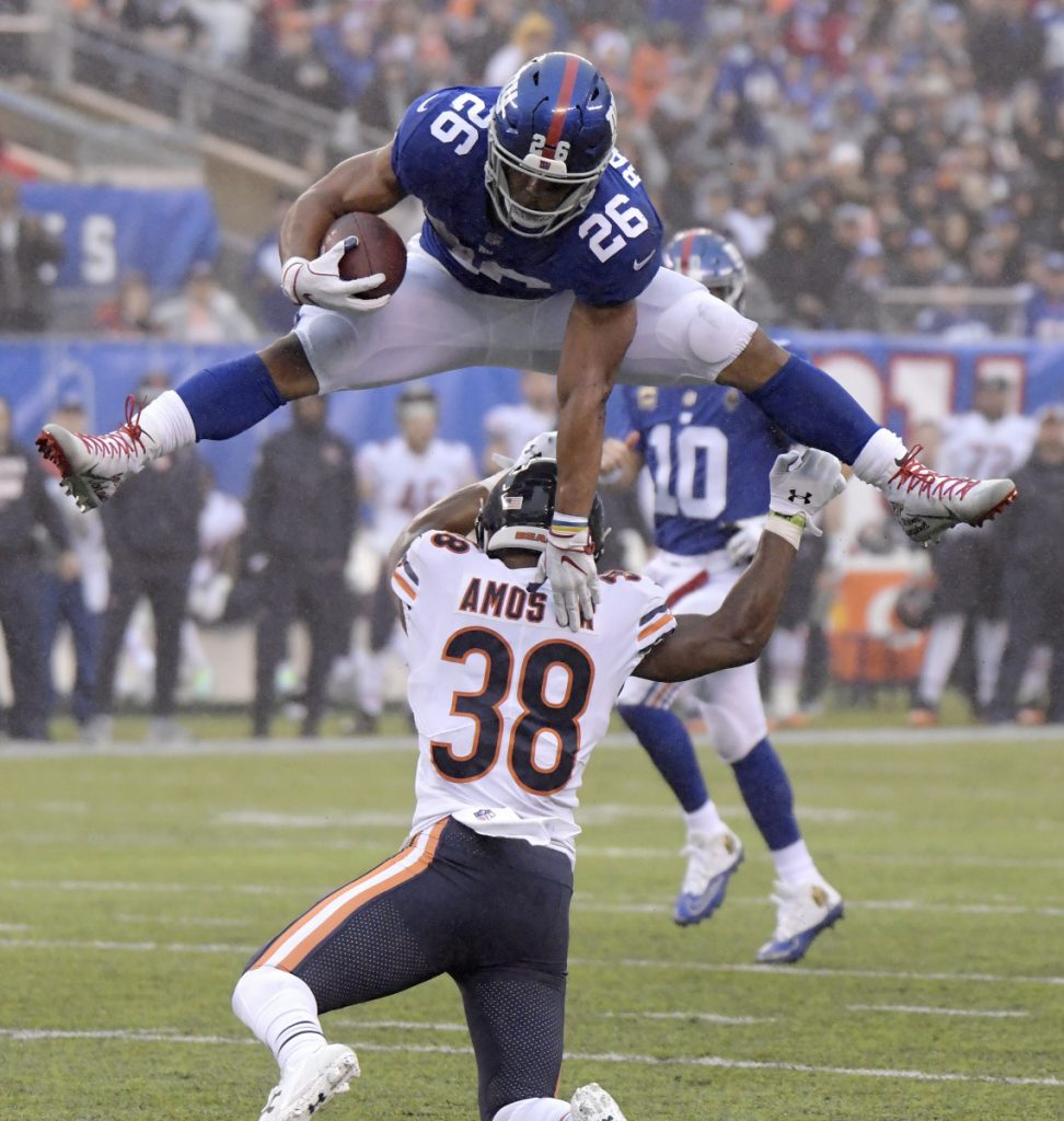 Giants running back Saquon Barkley leaps over Bears strong safety Adrian Amos on a 17-yard reception during New York's 30-27 win on Sunday.