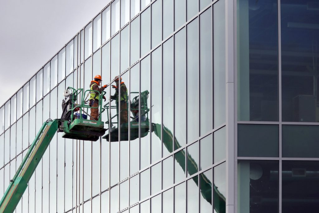 Anthony Richards trims out newly installed windows last week at the Wex building that's under construction on Thames Street in Portland. CMP billed a company working on the building for only a fraction of the 43,000 kilowatt-hours it used.