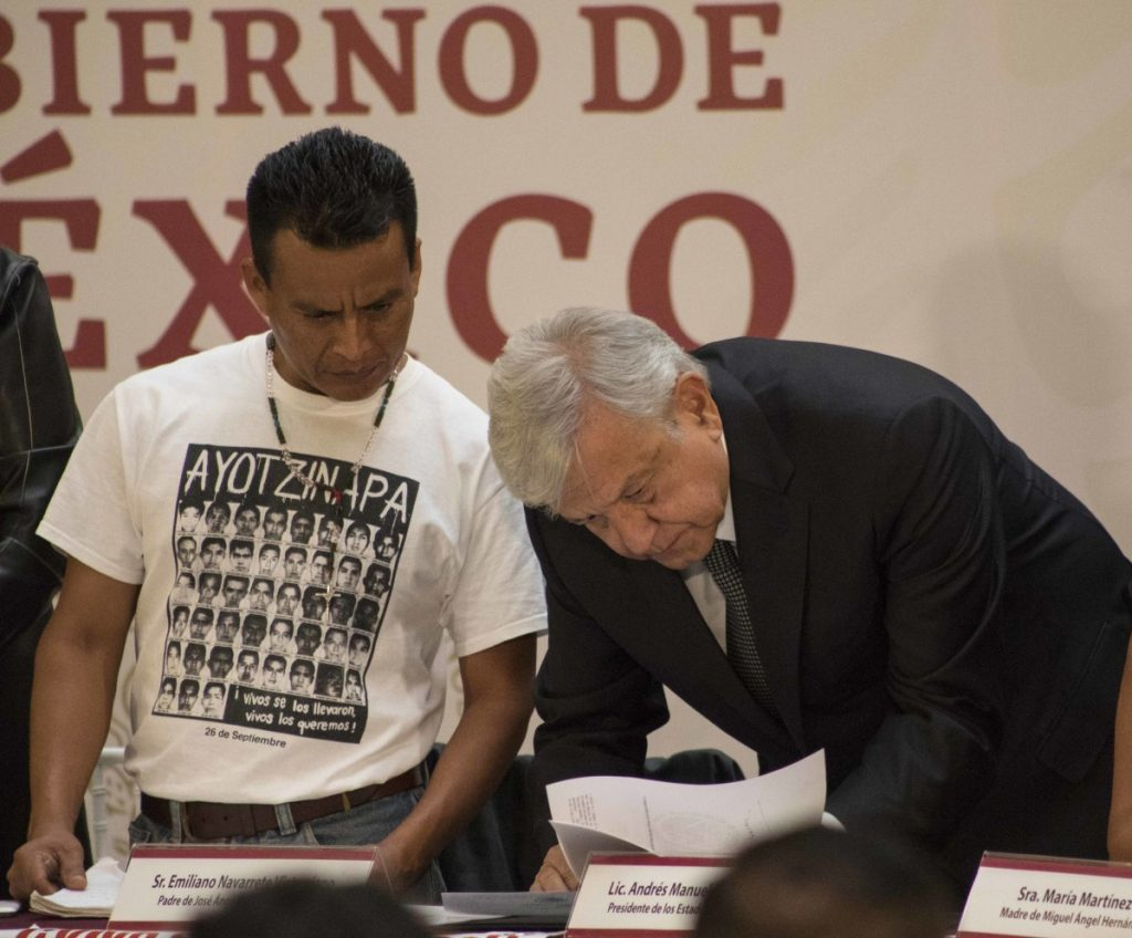 Mexican President Andres Manuel Lopez Obrador signs a decree Monday creating a truth commission to probe the 2014 disappearance of 43 students. AP Photo/Christian Palma