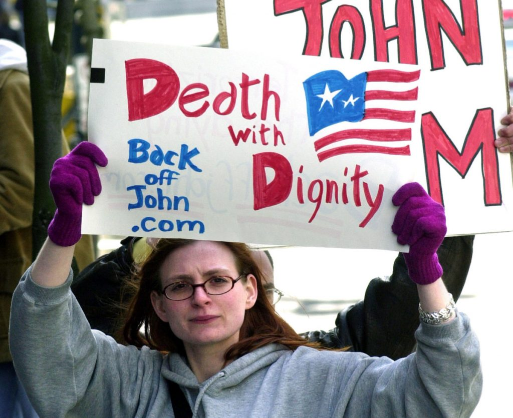 A protester calls for death with dignity during a 2002 hearing on Oregon's assisted-suicide law. A Maine doctor says that in his experience, the fears about such laws aren't valid.