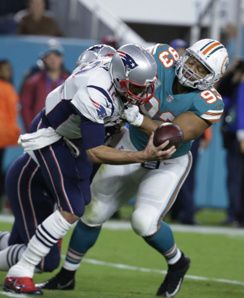 New England Patriots quarterback Tom Brady (12) is sacked by Miami Dolphins defensive tackle Ndamukong Suh (93), during the second half of an NFL football game, Monday, Dec. 11, 2017, in Miami Gardens, Fla. (AP Photo/Lynne Sladky)