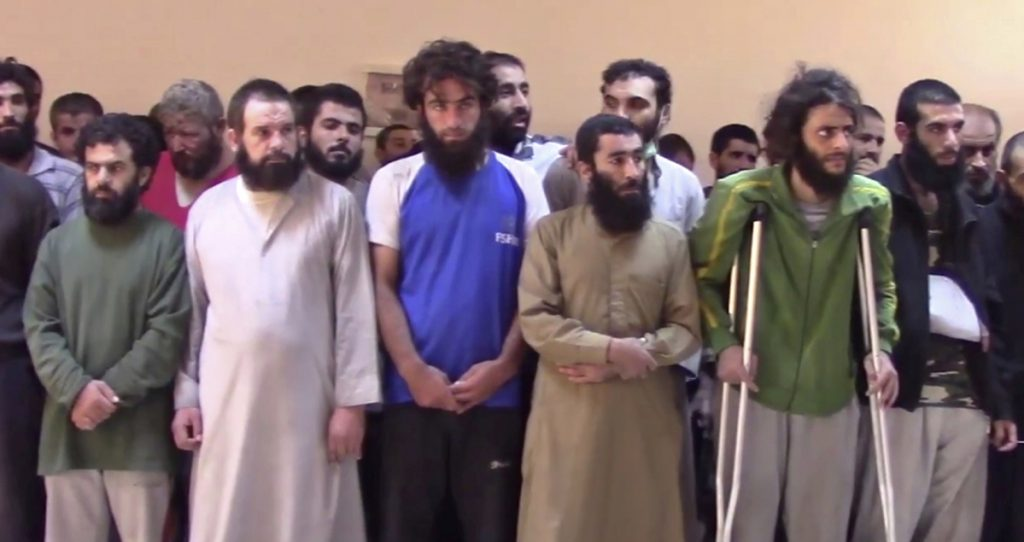 Syrian Islamic State group fighters who surrendered stand at a base of the U.S.-backed Syrian Democratic Forces in October 2017.