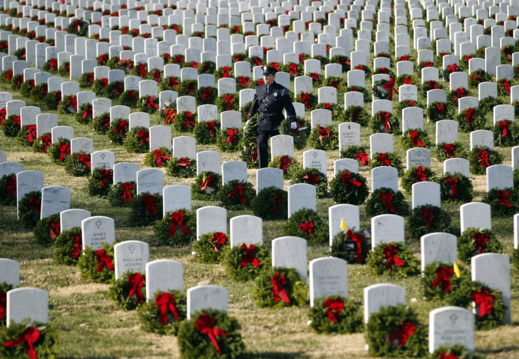 Portland police Officer Terry Fitzgerald places wreaths at Arlington National Cemetery in 2012. Maine's Wreaths Across America has seen its revenues skyrocket from $227,000 in 2011 to $14.6 million last year.