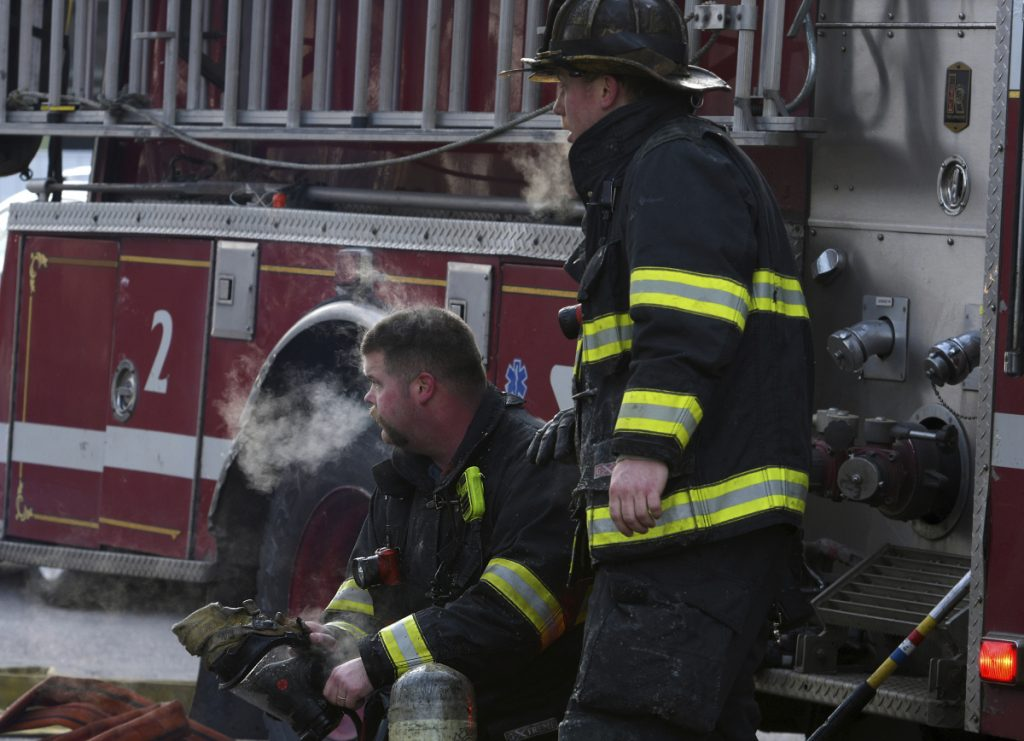 Firefighter Michael Brotherton, left, and a colleague rest for a moment while responding to a fire at an apartment building Sunday in Worcester, Mass. A Massachusetts firefighter injured while battling the early morning blaze has died, officials said.