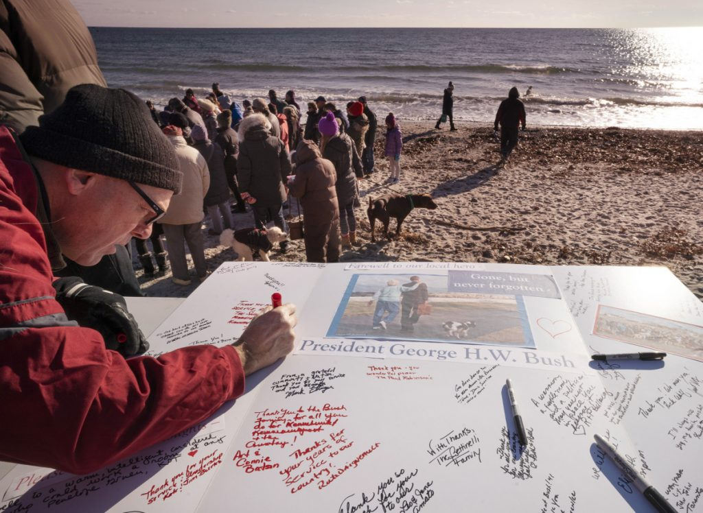 Chris Snow of Kennebunk signs a card in honor of the late President George H.W. Bush at Gooch's Beach in Kennebunk on Sunday. About 200 people gathered at the beach with their dogs to sign the card and share remembrances of the 41st president and his wife, Barbara. Mrs. Bush often walked her dogs on the beach.