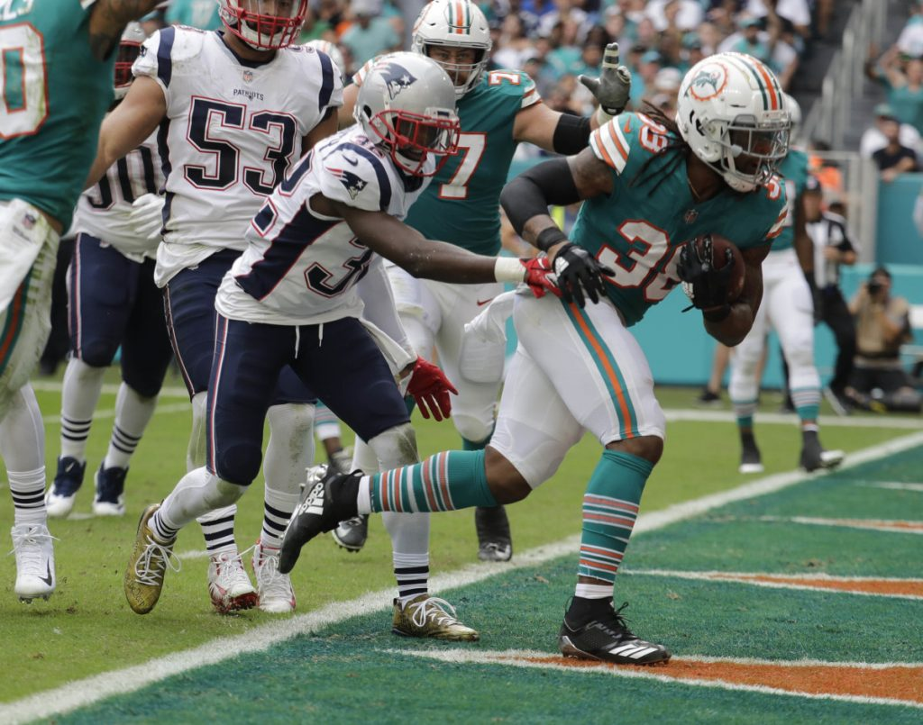 Dolphins running back Brandon Bolden scores one of his two touchdowns Sunday against his former team, helping Miami beat the Patriots, 34-33.