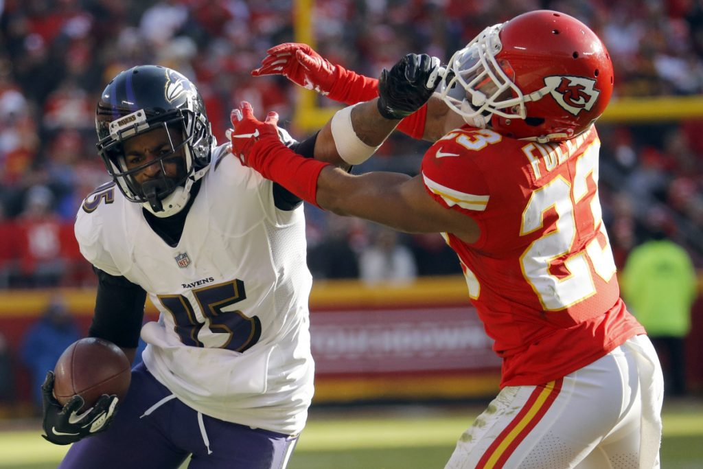 Ravens wide receiver Michael Crabtree tries to fend off Kansas City cornerback Kendall Fuller during the Chiefs' 27-24 overtime victory Sunday in Kansas City, Mo.