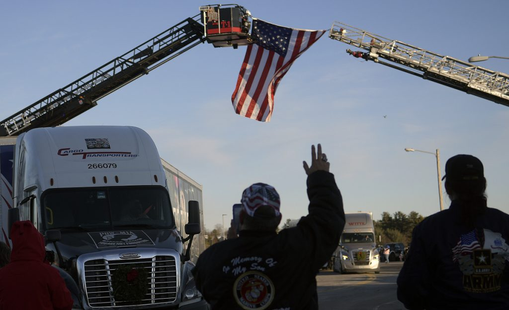 People greet tractor trailers carrying wreaths Sunday at the Augusta Civic Center on the first leg of the Wreaths Across America trip from Maine.