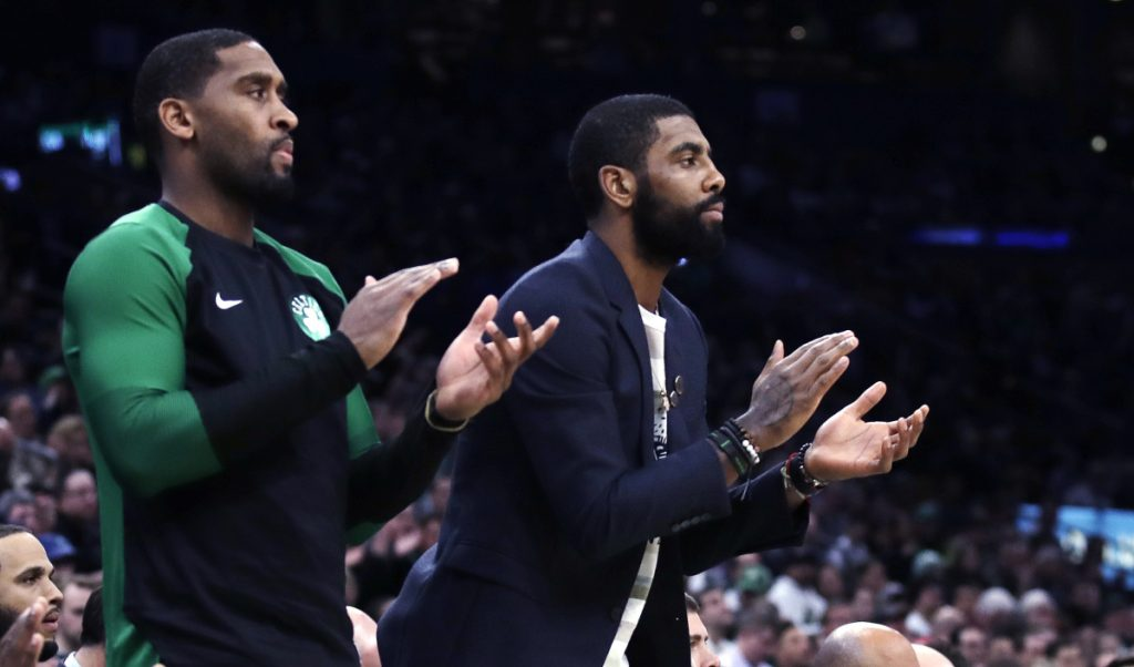 Boston Celtics guard Kyrie Irving, right, who did not play due to an injury, and guard Brad Wanamaker, left, applaud teammates during the first quarter of the Celtics' 113-110 win over New Orleans on Monday in Boston.