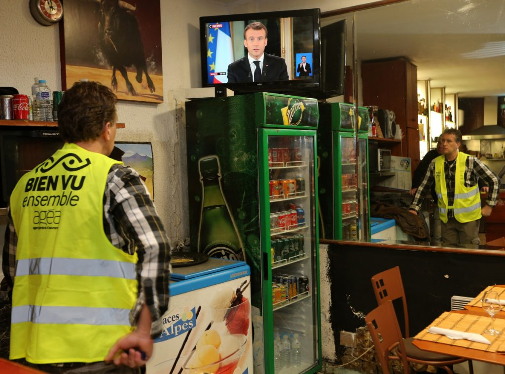 Yohann Piedagnel watches French President Emmanuel Macron during a televised address to the nation, in Hendaye, southwestern France, Monday. In an unusual admission, French President Emmanuel Macron says he's partially responsible for anger fueling protests.