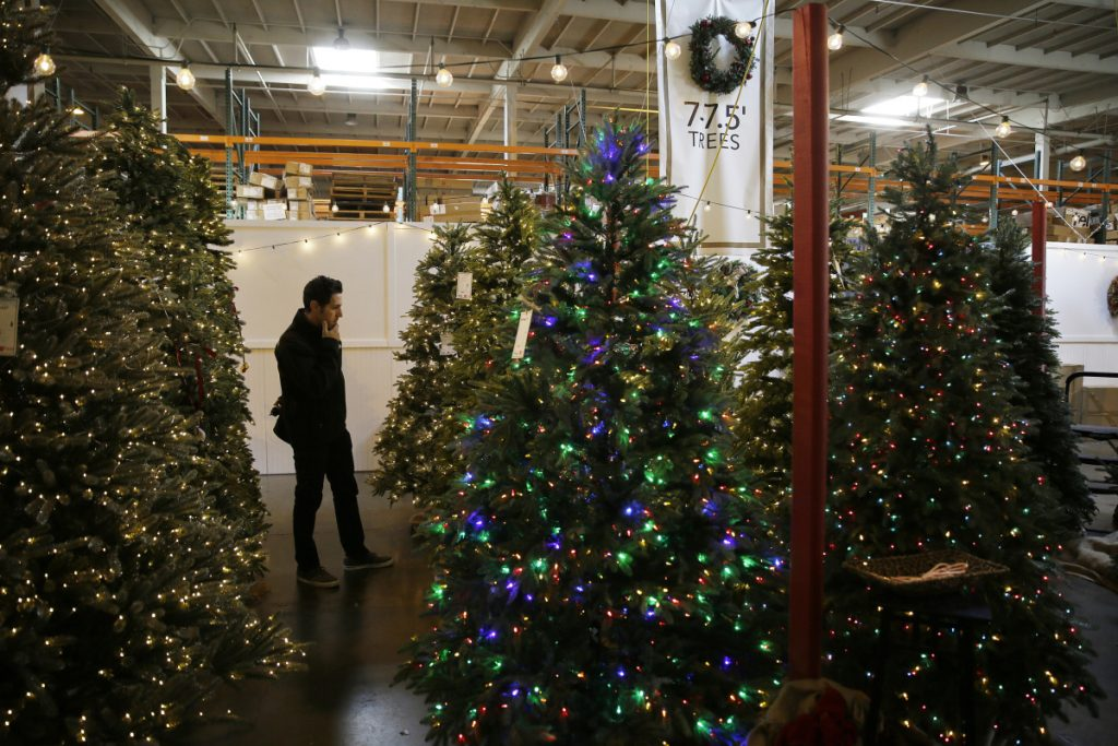 A shopper looks over his options recently at a Burlingame, Calif., outlet store of Balsam Hill, the leading retailer of artificial Christmas trees. About 80 percent of Americans who put up a holiday tree now use a fake one, so tree farmers hope to persuade millennials to go with the real thing as they begin forming traditions with their children.