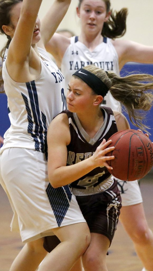 Freeport's Abby Brier looks for an open teammate while being guarded by Yarmouth's Clementine Blaschke, left, and Hope Olson during the Falcons' 39-30 win in Yarmouth on Tuesday night.