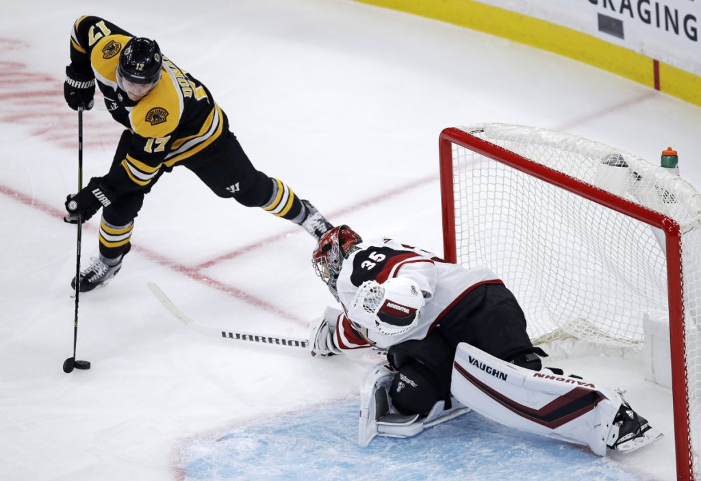 Arizona Coyotes goaltender Darcy Kuemper, right, sweeps his stick as he tries to break up a drive to the net by Boston Bruins center Ryan Donato (17) during the first period of an NHL hockey game in Boston, Tuesday, Dec. 11, 2018. (AP Photo/Charles Krupa)