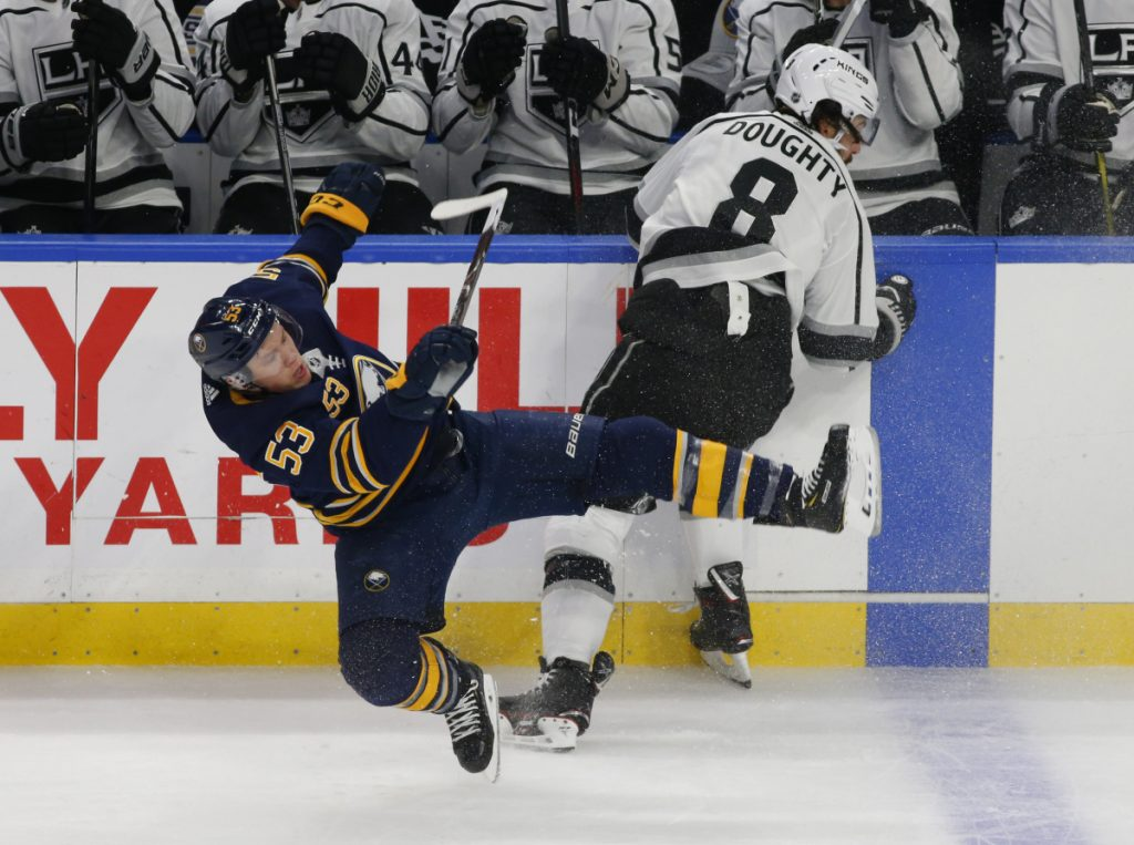 Sabres forward Jeff Skinner, left, is checked by Kings defenseman Drew Doughty during the first period Tuesday in Buffalo, N.Y. Skinner scored in overtime for a 4-3 Buffalo win.