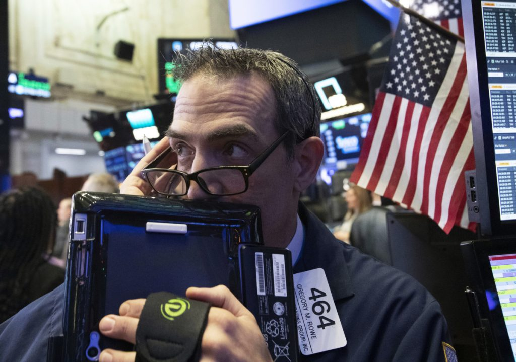Trader Gregory Rowe works at the New York Stock Exchange on Dec. 12 in New York. Stocks suffered losses Monday.