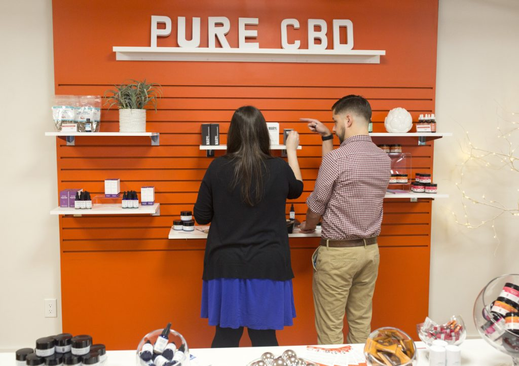 Wellness Connection employees Sarah Anderson and David Theberge label the wider selection of cannabidiol products that the Portland dispensary can now sell under new state regulations. Customers 21 and older can buy hemp products without a medical marijuana card from a doctor.