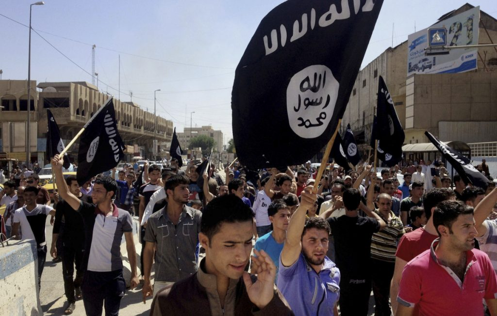 Demonstrators chant pro-Islamic State slogans in 2014 in front of the provincial government headquarters in Mosul, Iraq. President Trump says the group is defeated, but it has stockpiled enough cash to finance terrorist operations for years.
